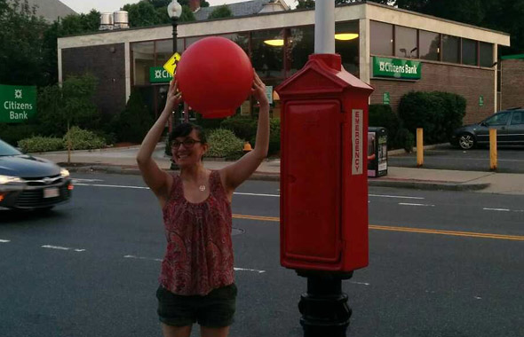 Woman holds giant red ball in Brighton