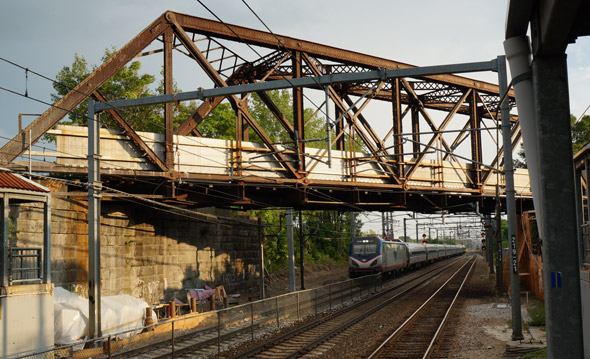 Amtrak train under old bridge in Readville
