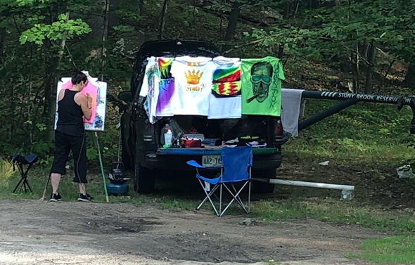 People selling T-shirts in the forest