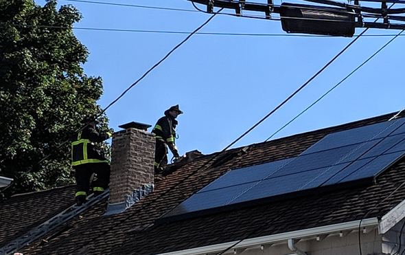 Firefighters on roof in Roslindale
