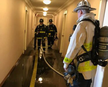 Firefighters in Hawthorne Place hallway