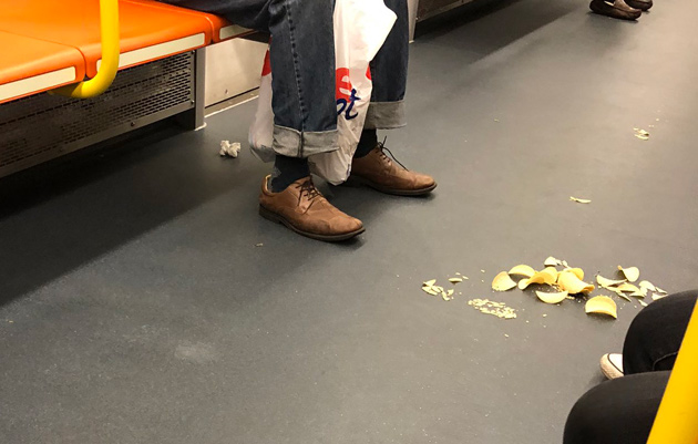 Chips, other trash on the floor of a new Orange Line car