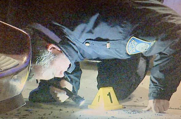 Officer looking for evidence at shooting scene on Crawford Street in Roxbury