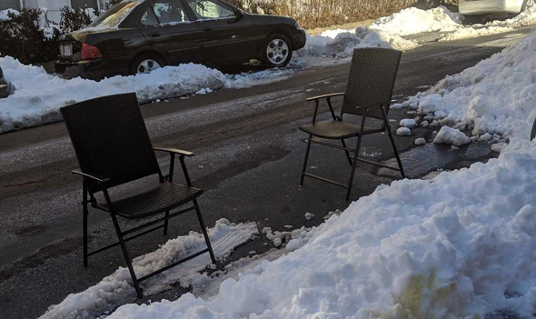 Two chairs used as space savers on Sutherland Road in Brighton