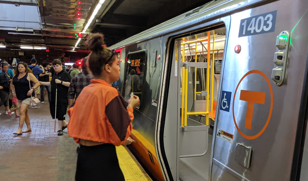 Woman in orange gets on the Orange Line at Forest Hills