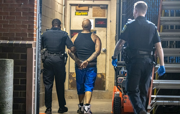 Suspect being walked into police station