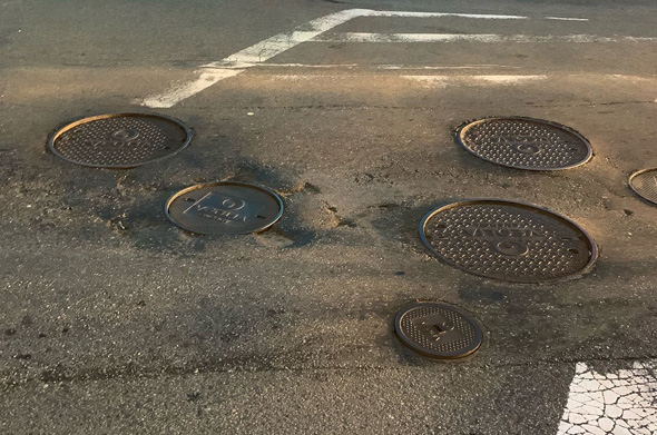 Multiple potholes and Veolia manhole covers