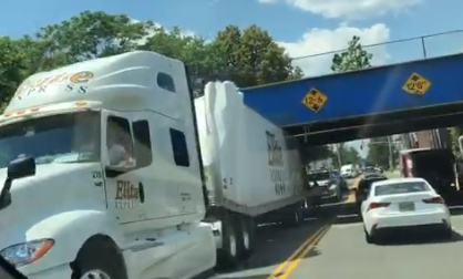 Truck wedged under an Orange Street bridge in Malden