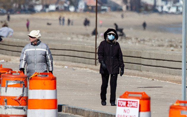 Woman walking past barrels at Revere Beach