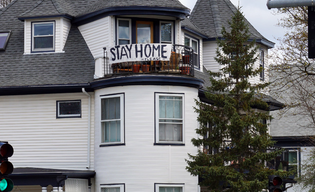 Banner in Roslindale that says: Stay home!