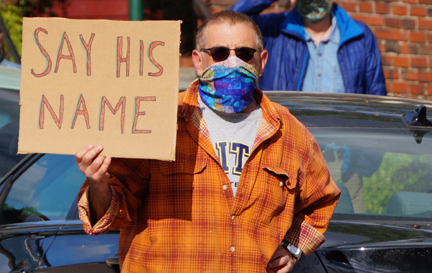Man with sign: Say his name