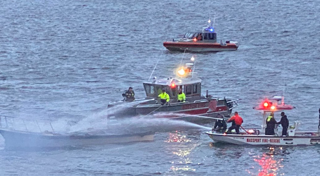 Boston and Massport fire crews pour water on burning boat