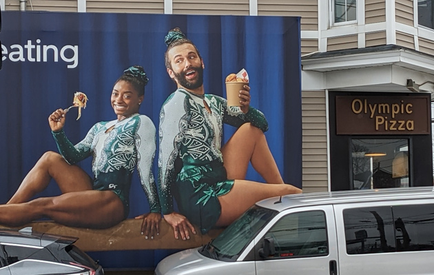 Simone Biles and a Queer Eye guy on the side of Olympic Pizza