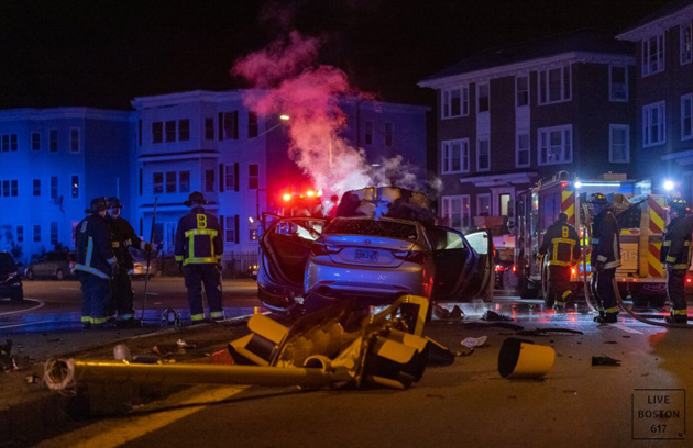 Crash scene in Mattapan - traffic light destroyed, car bursts into flames