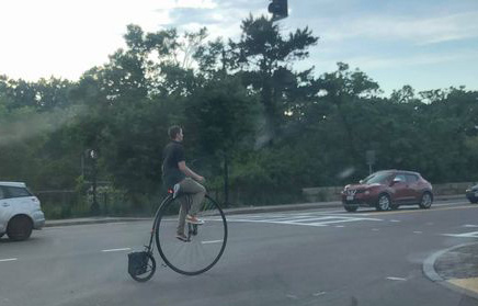 Guy riding a penny farthing in Forest Hills