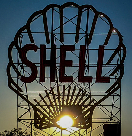 Sun coming through the Shell sign on Memorial Drive at sunset