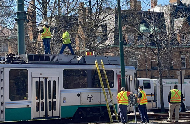 Workers atop a Green Line trolley on Beacon Street