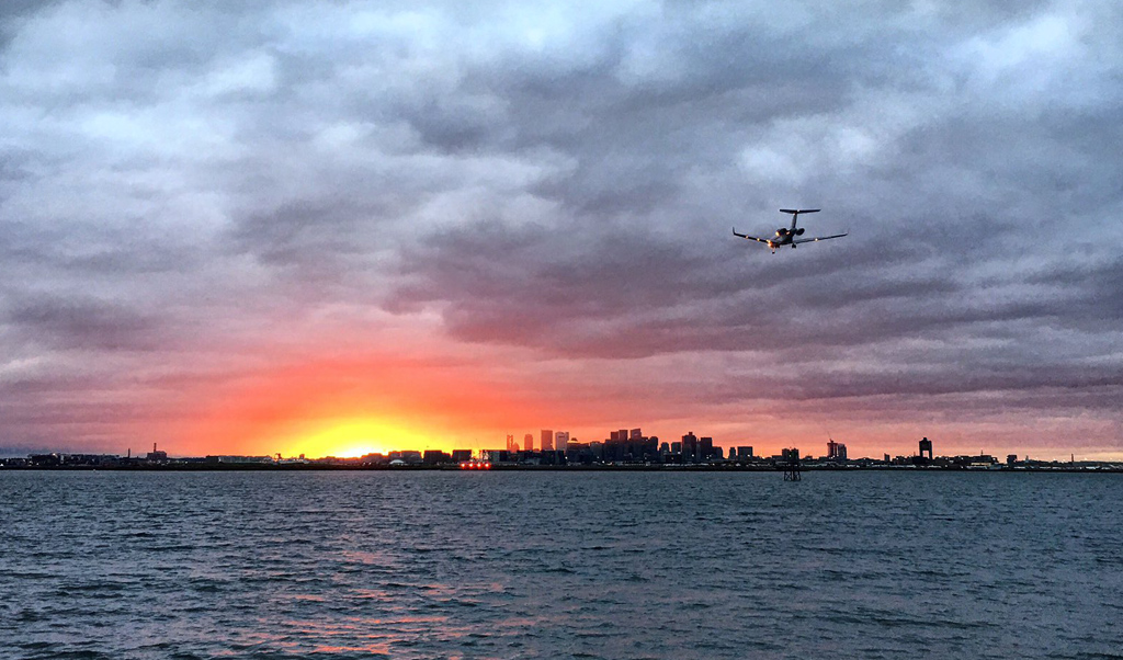 Plane flying into the sunset over Boston Harbor