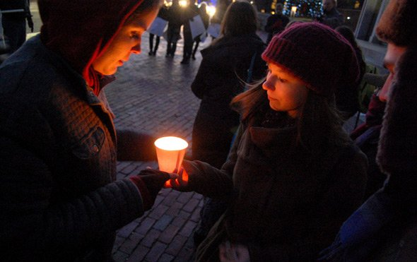 People holding a protest candle in front of the State House