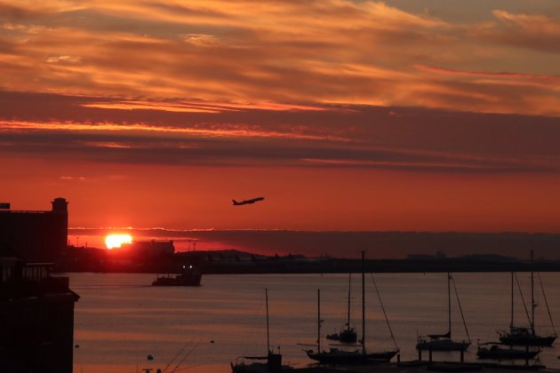 Sunrise over Boston Harbor with a plane taking off