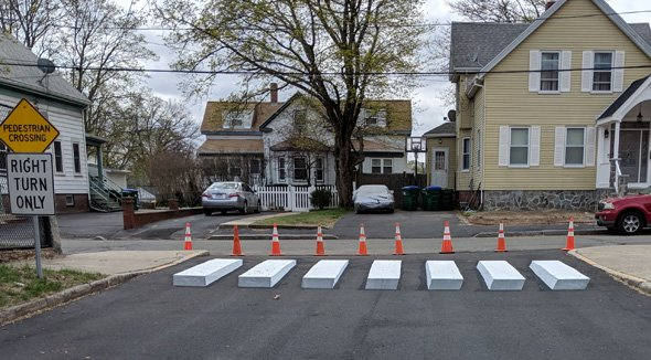 Apparent concrete blocks at exit of Brooks School parking lot