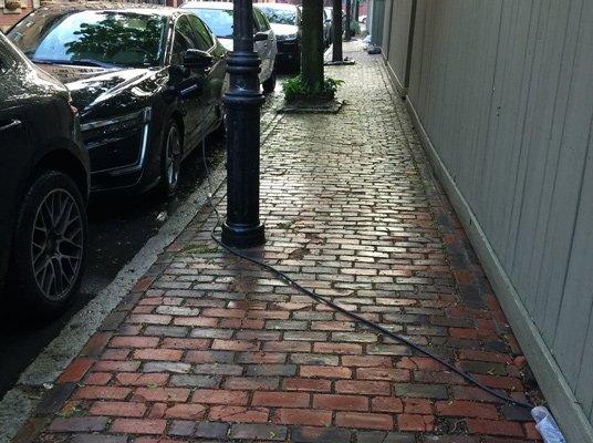 Electric-car charging cord on sidewalk