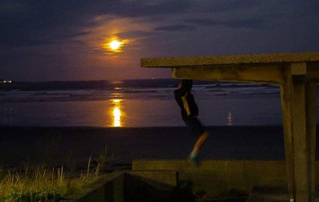 Man doing pullups under a full moon in Lynn