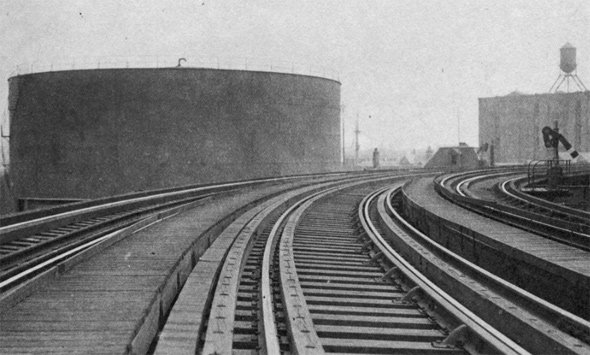 Molasses tank as seen from elevated railroad along Commercial Street