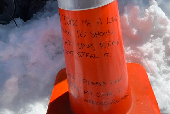 Traffic cone that urges reader not to take parking space or the cone itself in Allston