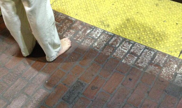 A man with no shoes on the Red Line