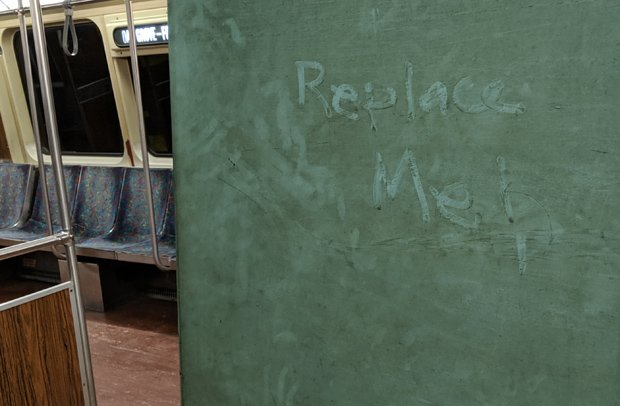 Replace Me written in thr grime on the side of an Orange Line car