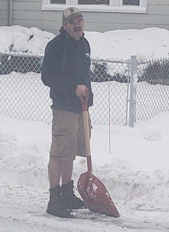Man shoveling snow in shorts in Watertown