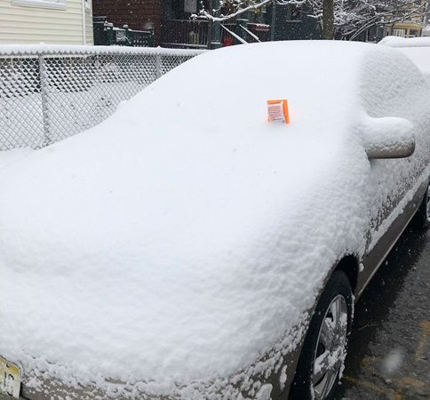 Car with a ticket in the snow in Jamaica Plain