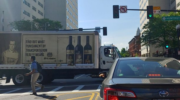 Truck blocking major intersection of Huntington Ave. and Massachusetts Ave. with sign that tells people they can find out what punishment by transportation means