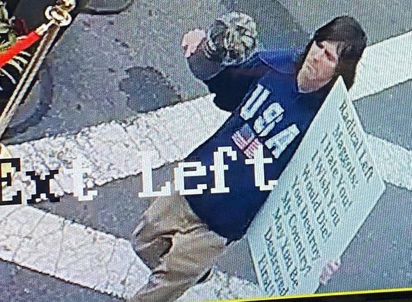 Guy with sign wishing death on people eating dinner outdoors in Marblehead