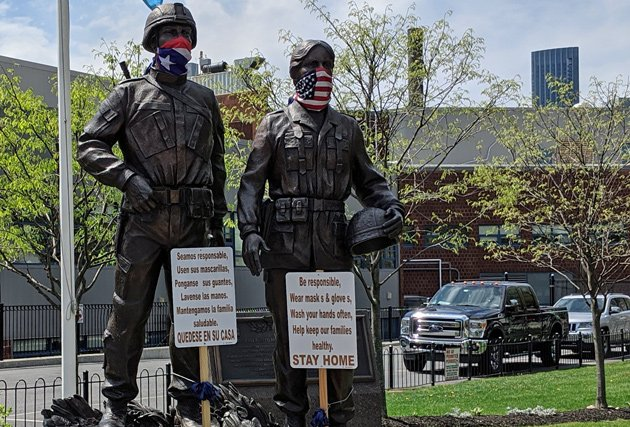 Statues of soldiers with masks in the South End urging people to stay home