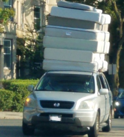 A lot of mattresses on one car in Brookline
