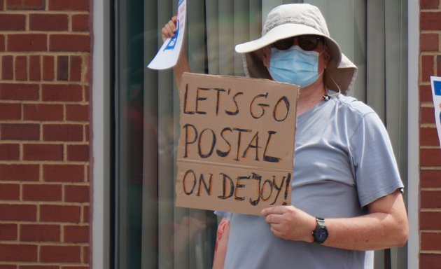 Man with sign that reads: Let's go Postal on DeJoy
