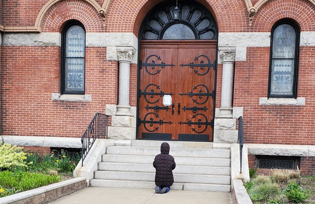 Woman praying outside closed church in Dorchester