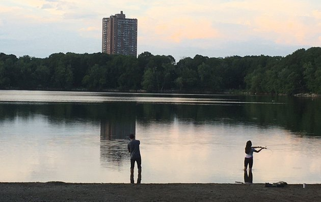 Two people fishing at Jamaica Pond at twilight