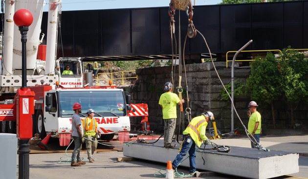 Workers on a piece of the new bridge at Robert Street