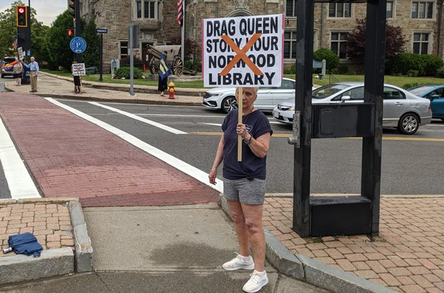 Woman holding sign against drag-queen story hour at the Norwood library