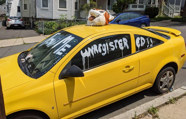 Abandoned car with a tiger head on it