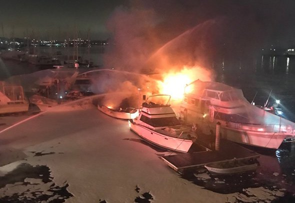 Boat on fire in Charlestown with lots of firefighting foam nearby