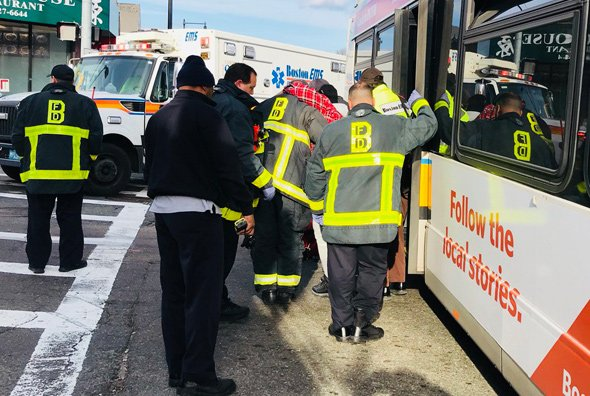 Firefighters help injured person from bus at Hyde Park Avenue and Canterbury Street