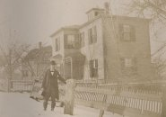 A man in his bowler hat in the snow in old Boston