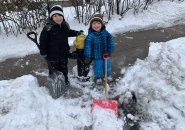Two kids shovel out a hydrant in Roslindale