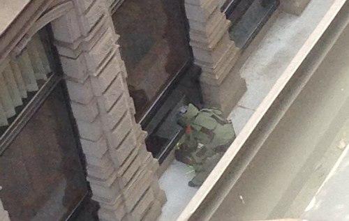 Bomb squad member investigates backpack