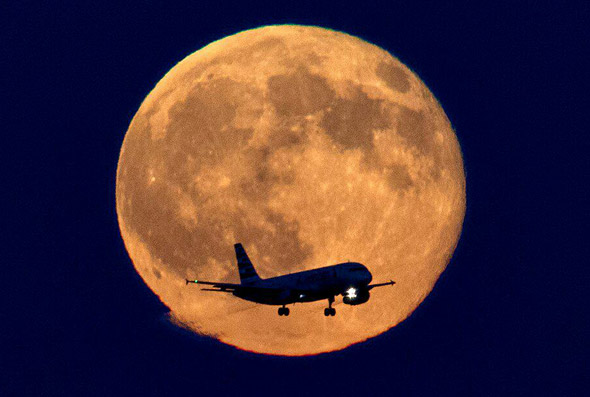 Airplane in front of blue moon