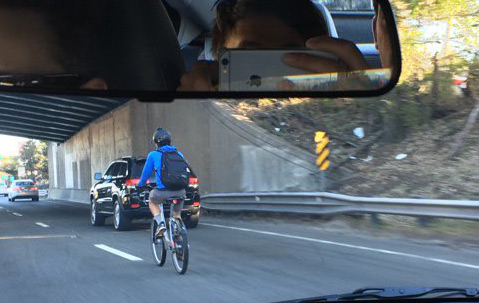 Hubway bicyclist on I-93 south in Dorchester